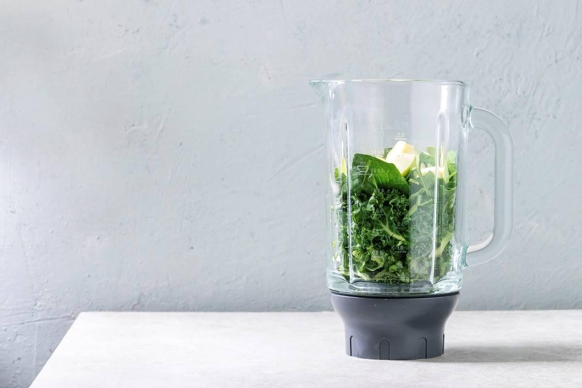 Vegetables and fruit sit in a blender.