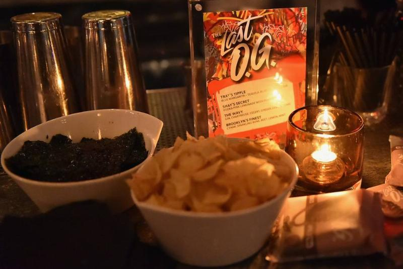 A bowl of chips is set out next to a candle at night.