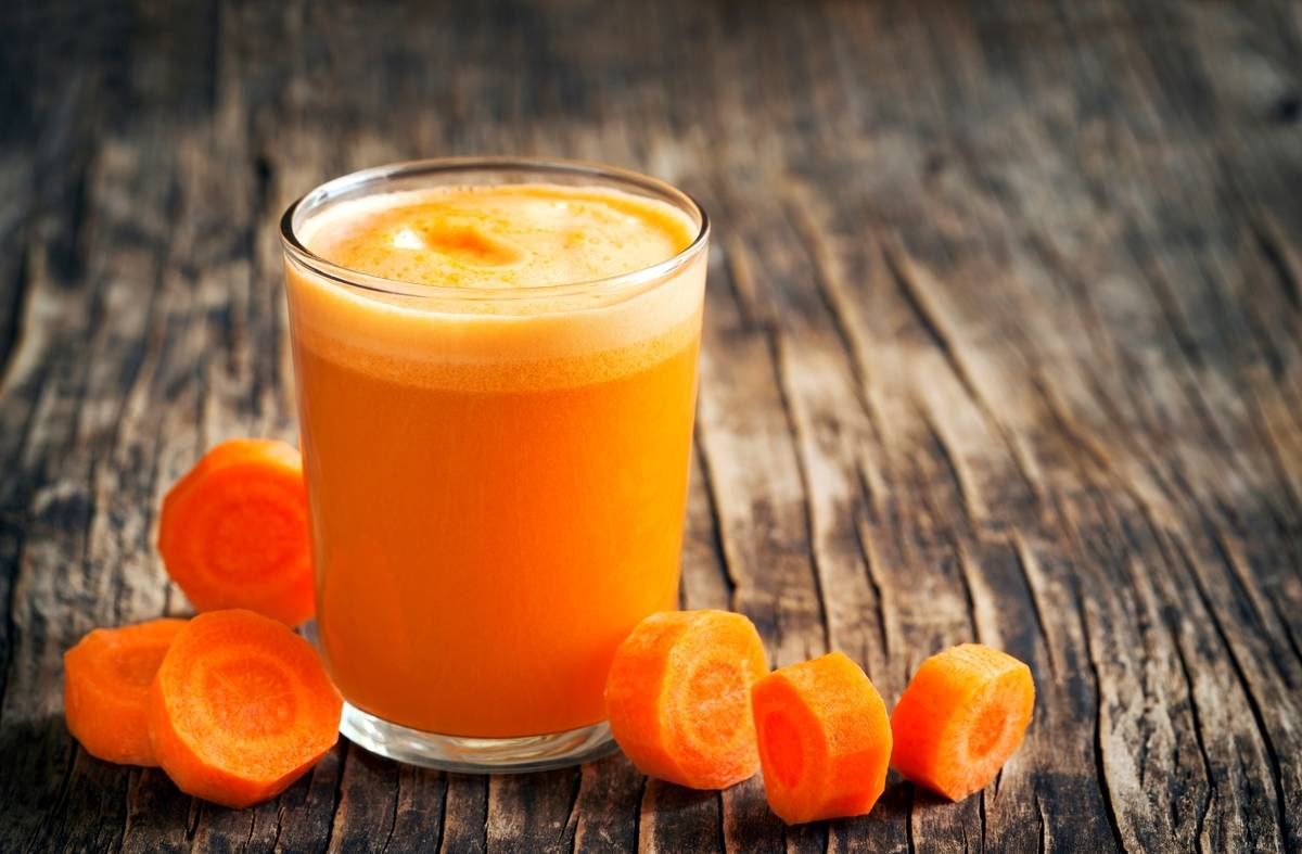 A glass of carrot juice is surrounded by slices of baby carrots.