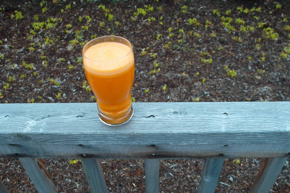 A glass of carrot juice sits on a balcony fence.