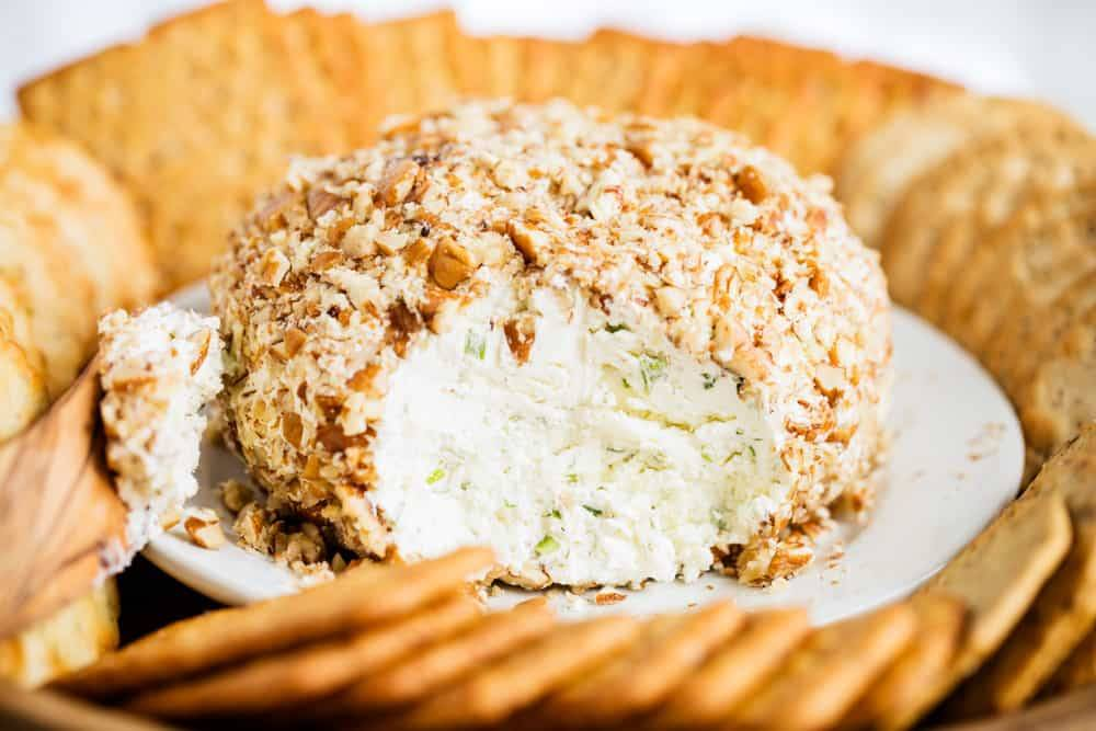 cheese ball covered in nuts with crackers
