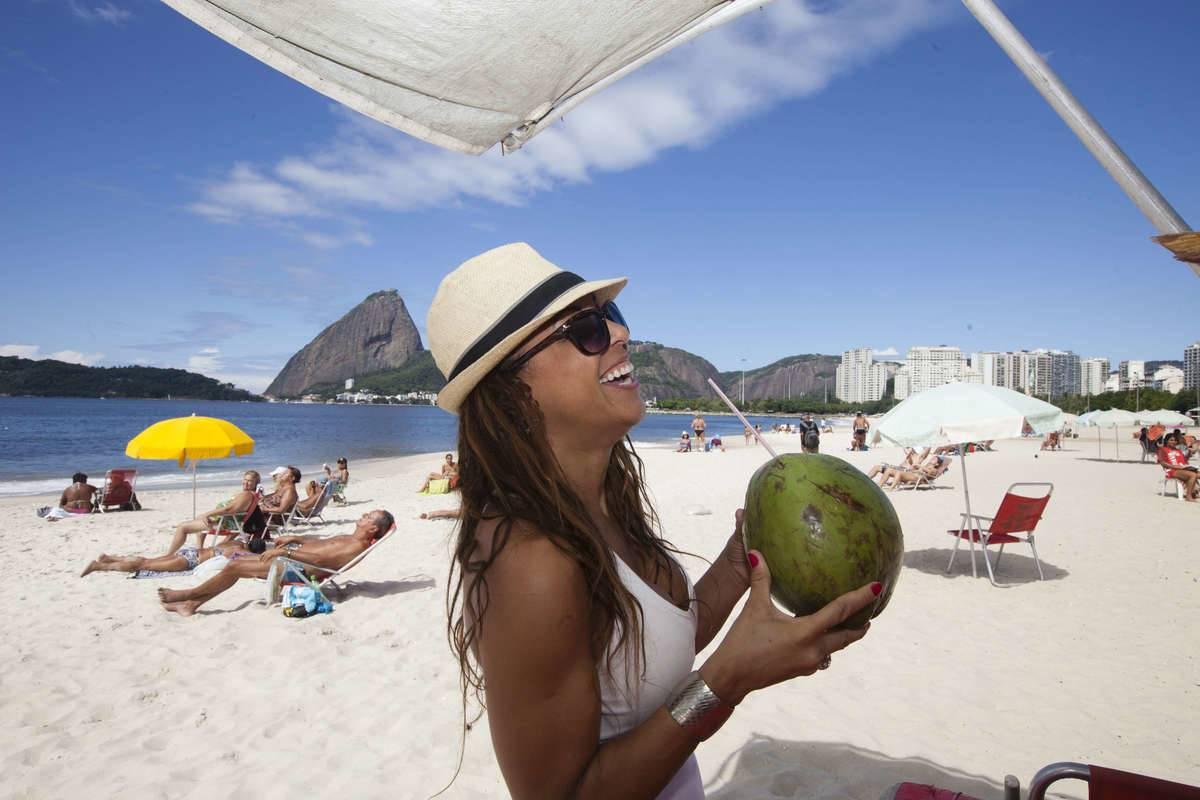 A woman drinks from a coconut on the beach in Brazil.