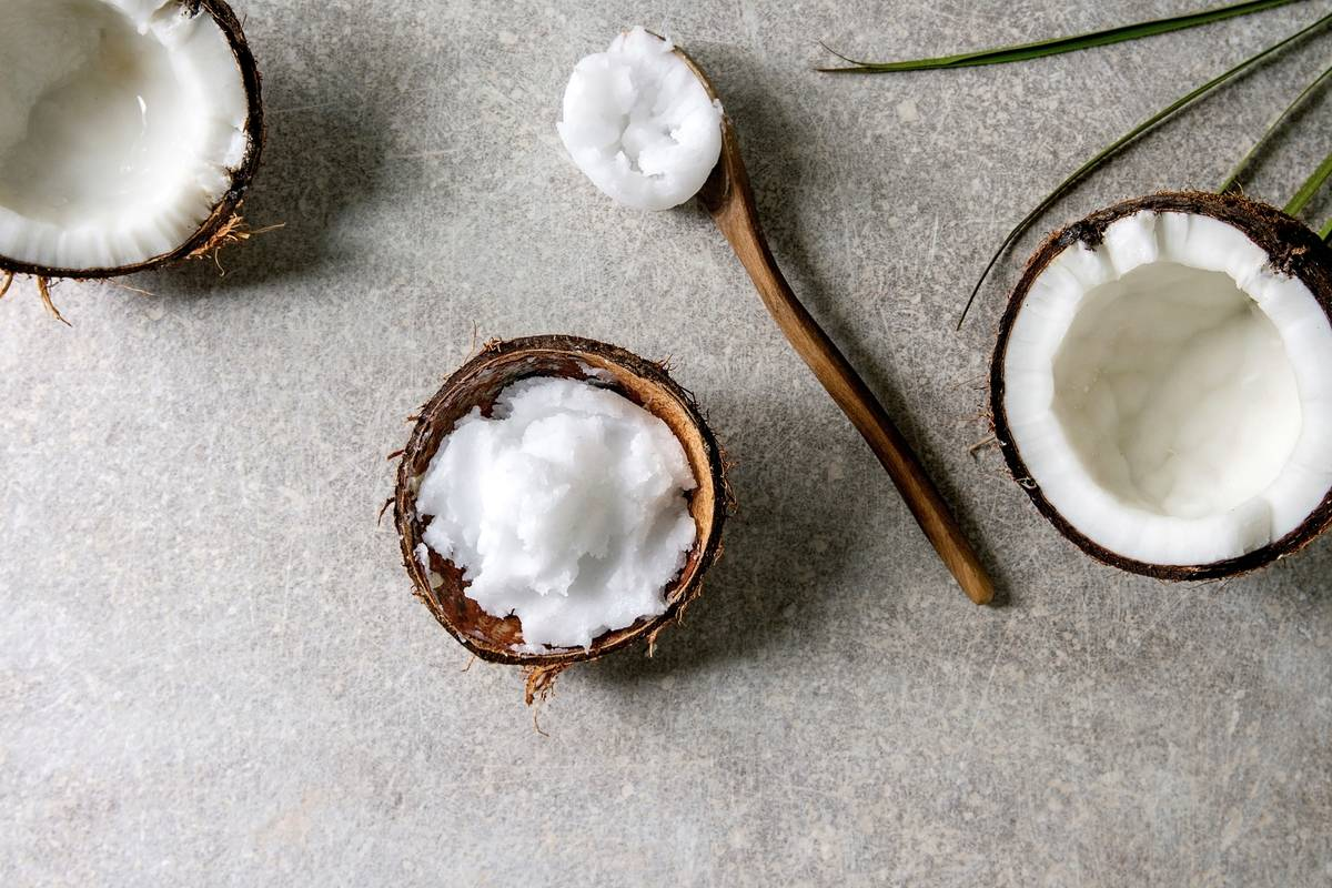 Coconut oil is scooped out of a coconut half.