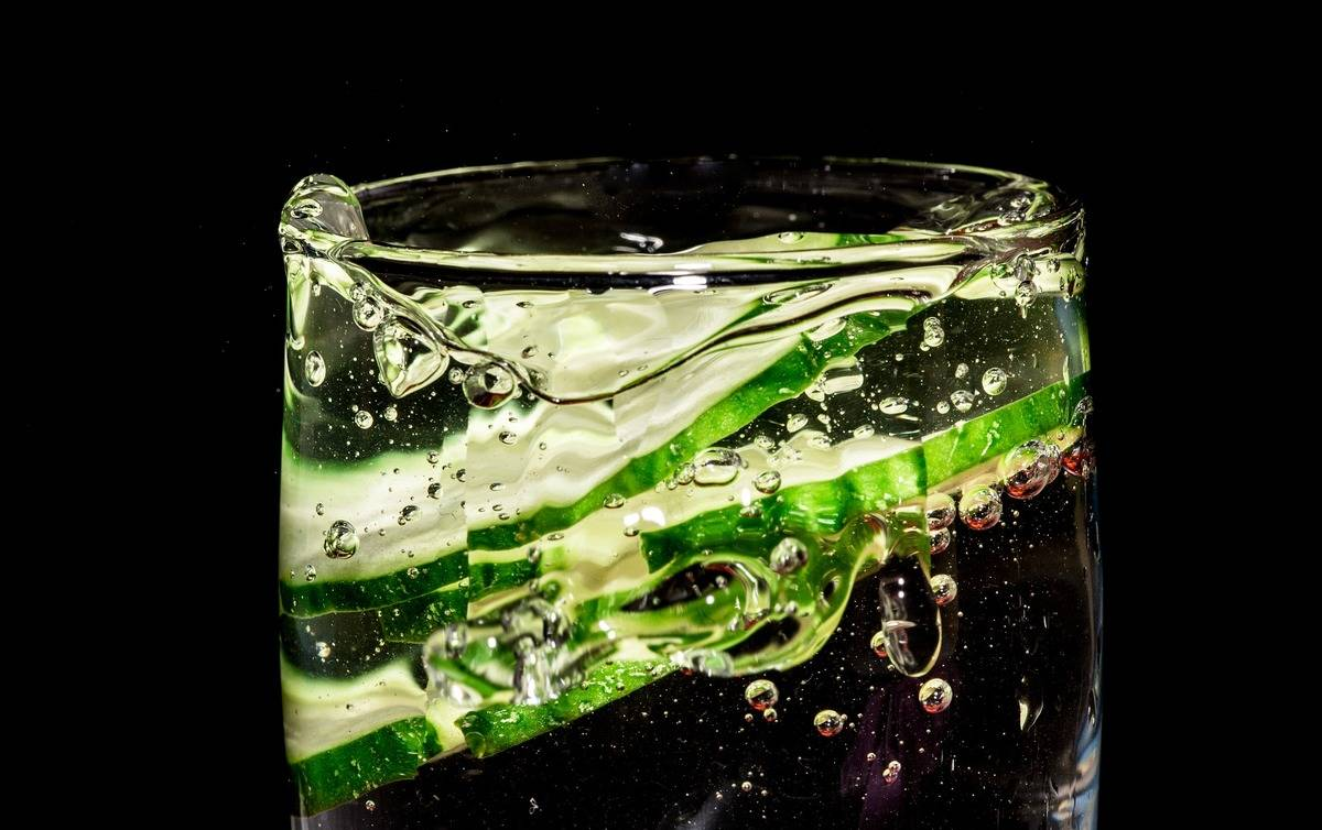 Cucumber slices splash into a glass of water.