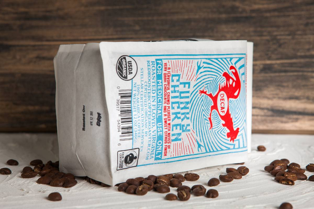 A Red Rooster is tipped over with decaf coffee beans around it.