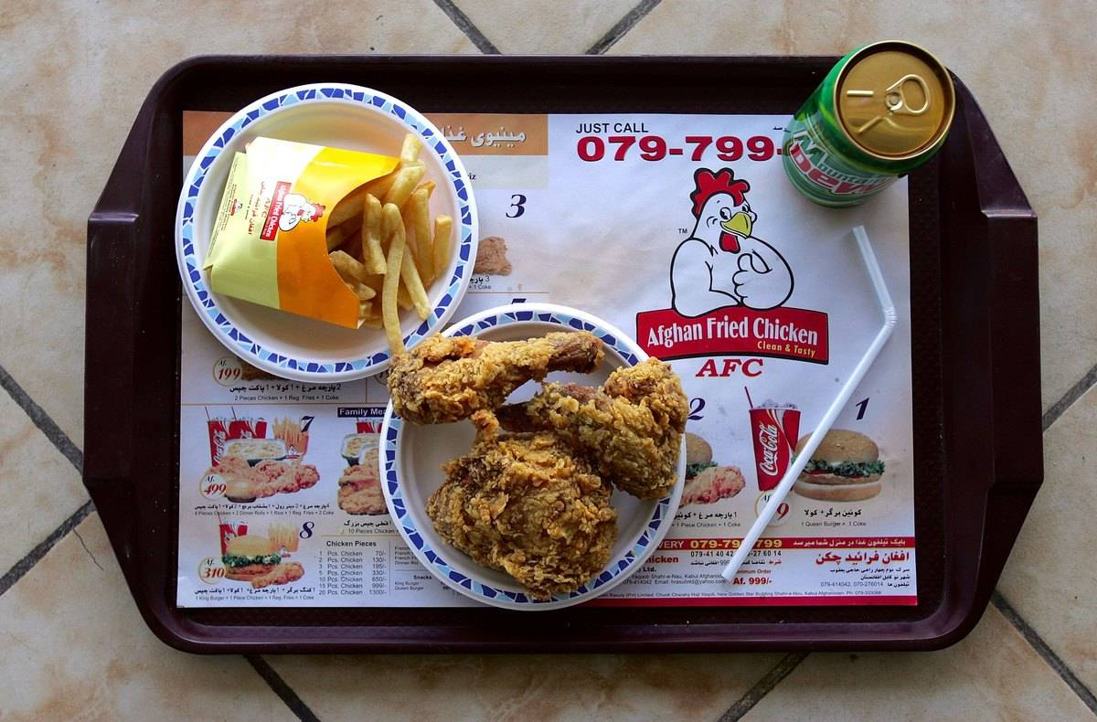 Fries and fried chicken are on a tray at a restaurant.