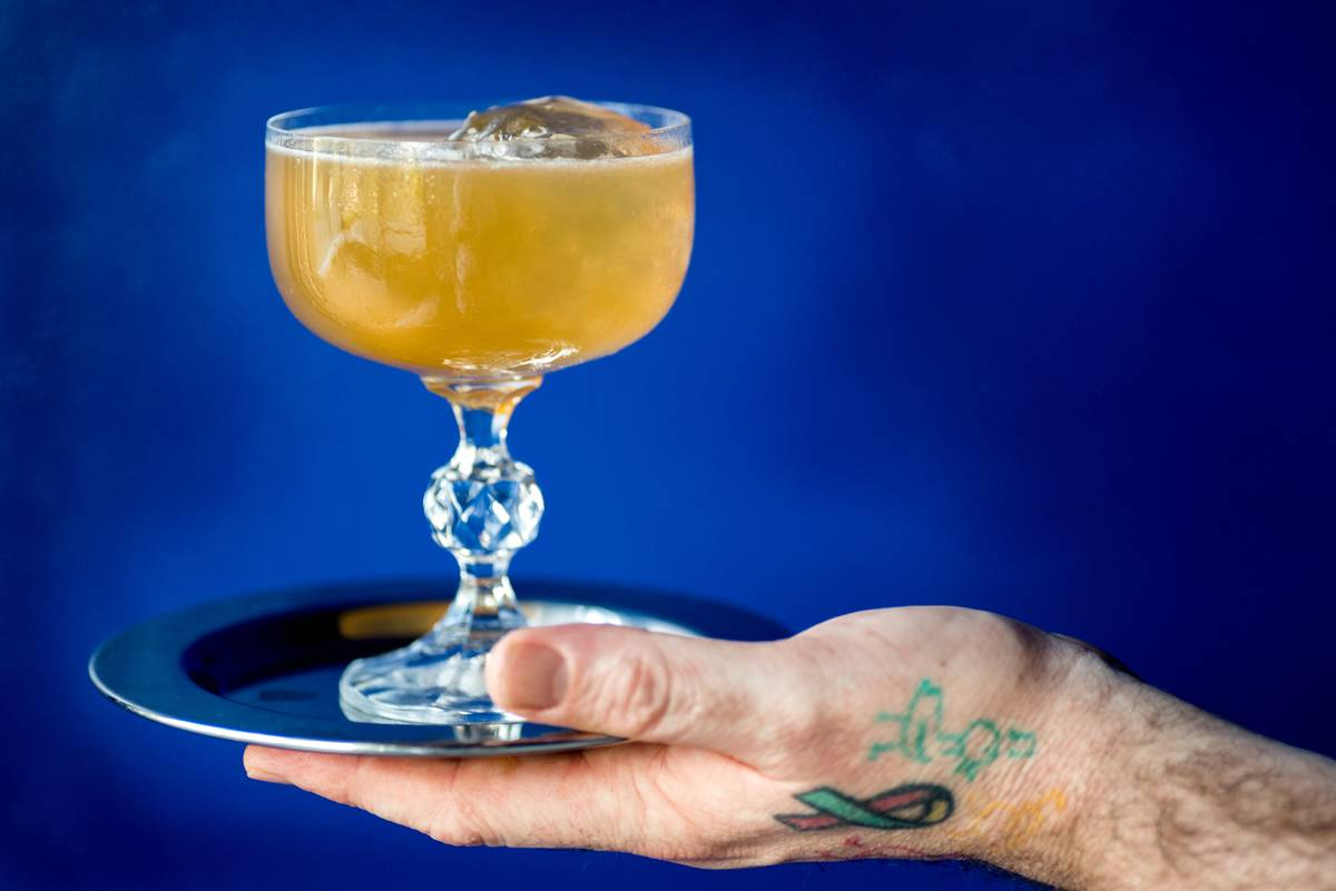 A person holds a glass containing a ginger honey cocktail.
