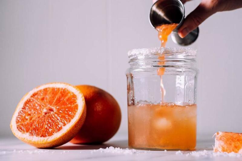 A person pours grapefruit juice into a glass.
