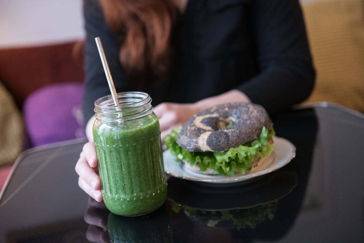 A woman enjoys a green smoothie with a bagel sandwich at a restaurant.