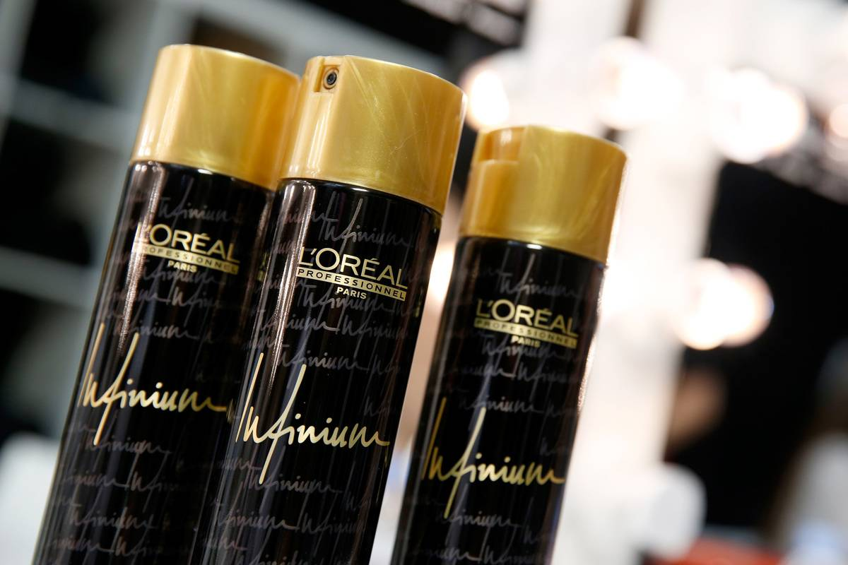 Three cans of L'Oreal hairspray are seen.