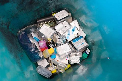 Used ink cartridges lie in the trash.