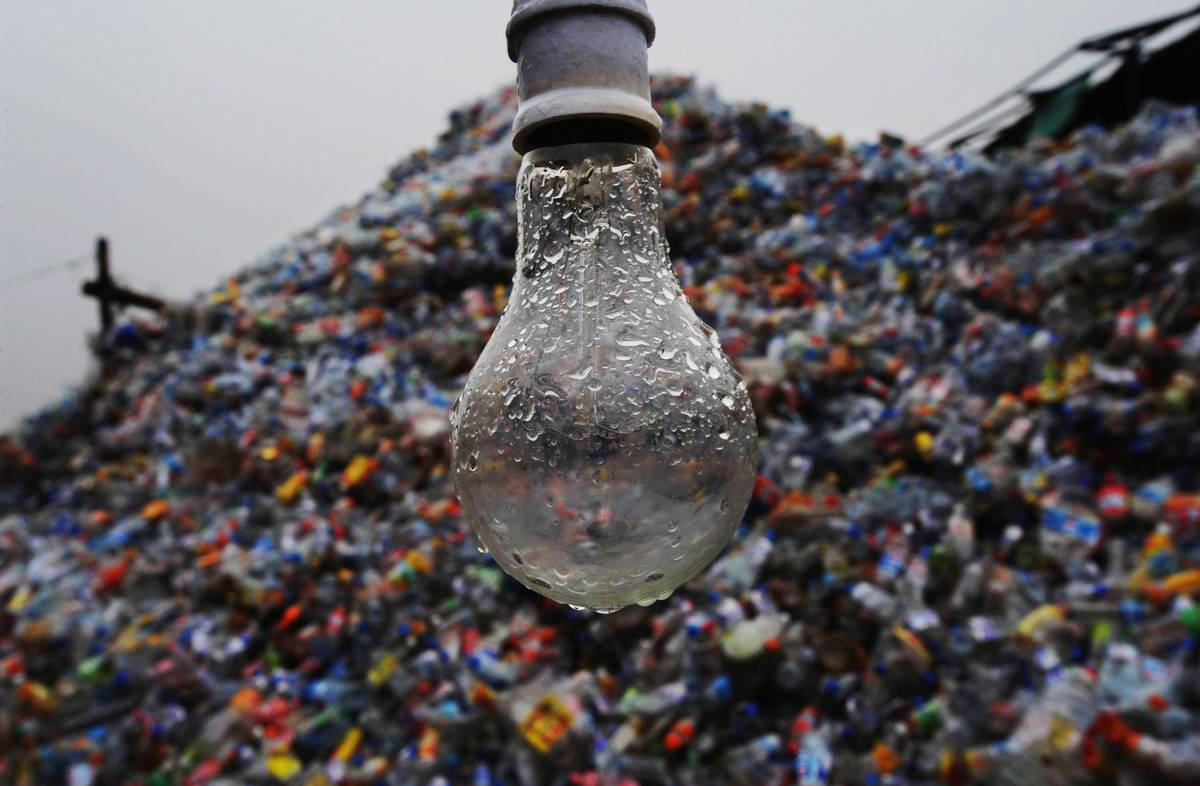 A wet light bulb appears in front of a landfill.