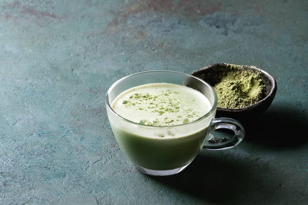 A matcha latte stands next to raw matcha powder.