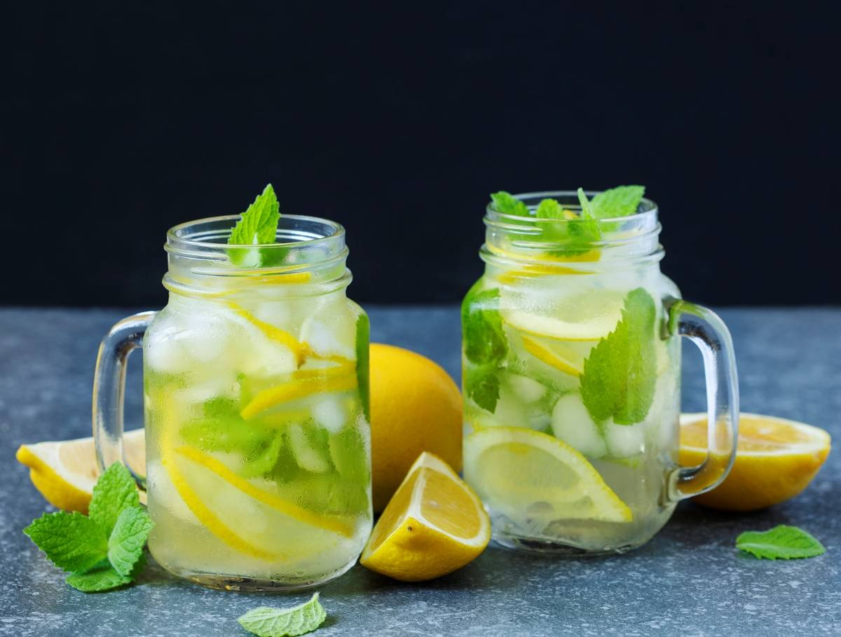 Two glasses of mint lemonade sit on a table.