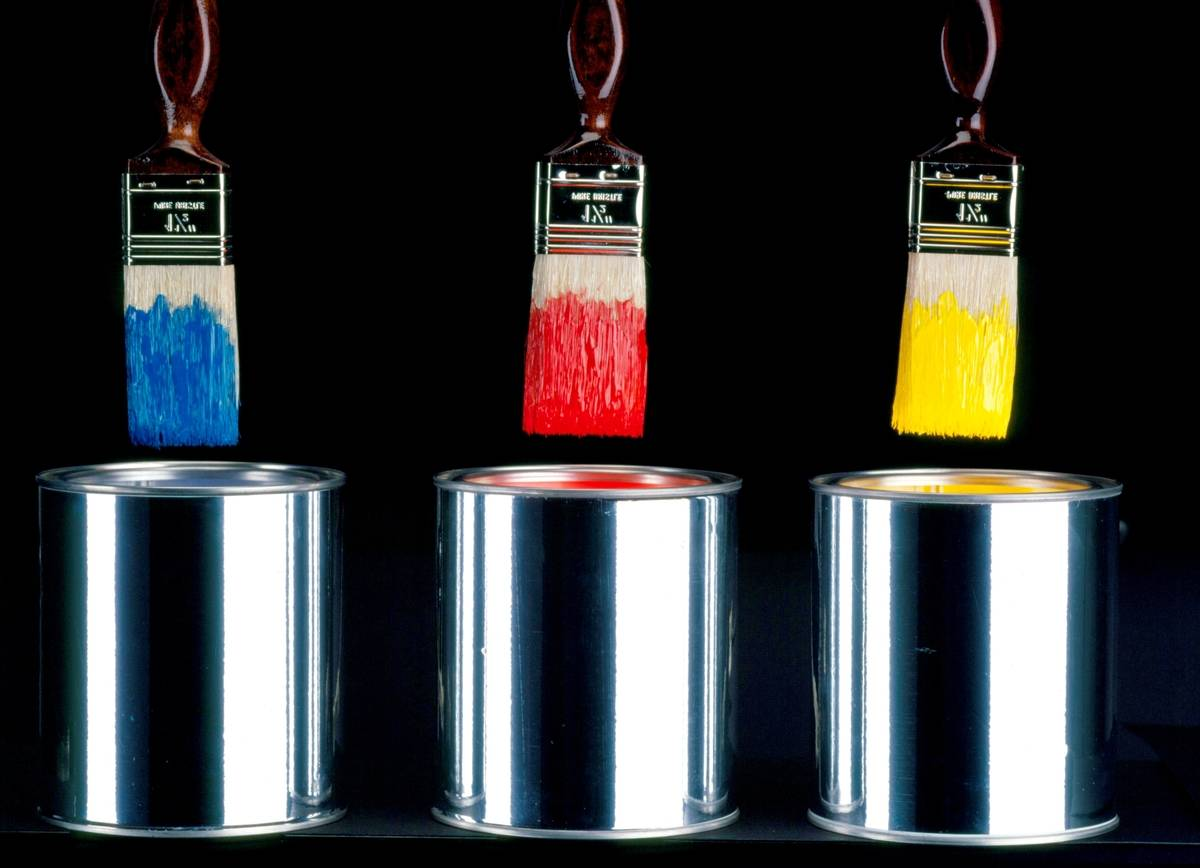 Paint brushes hover over tin cans.
