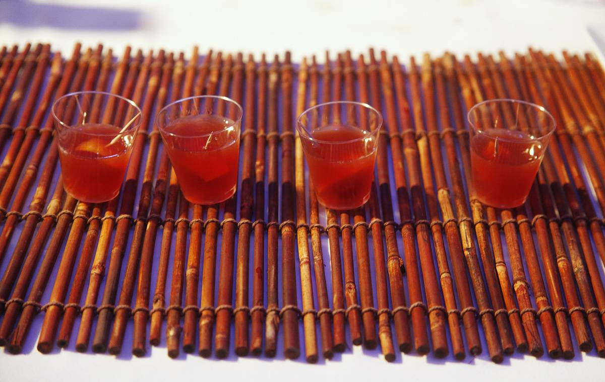 Cups of red pomegranate drinks stand on a mat made of sticks.