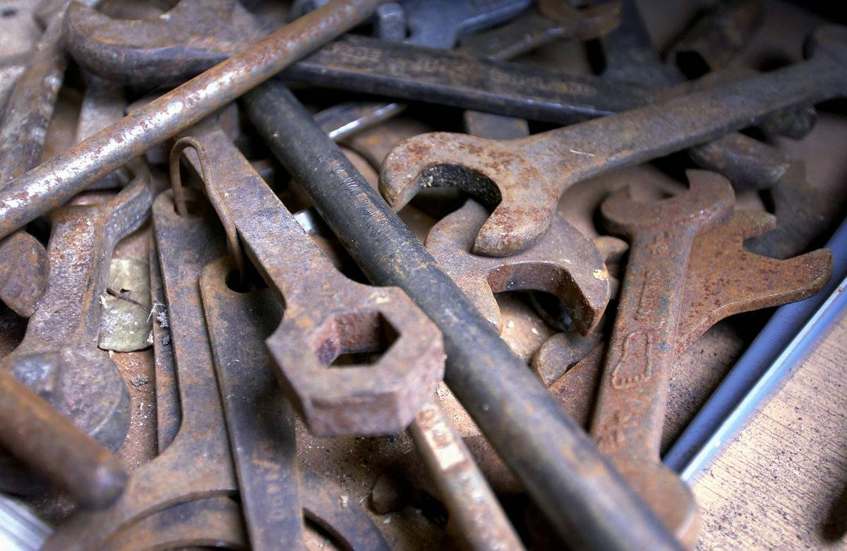 A pile of tools is covered in rust.