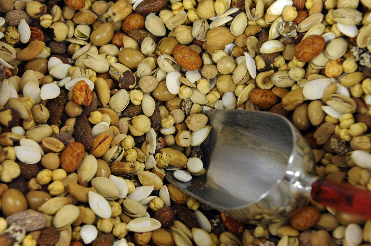 A scoop dips into a container of salted nuts.