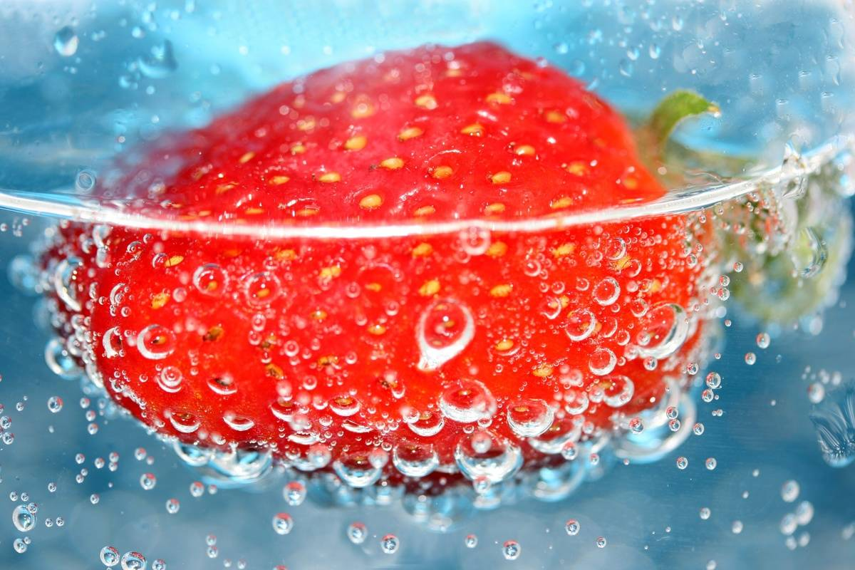 A close-up shows a strawberry in water.