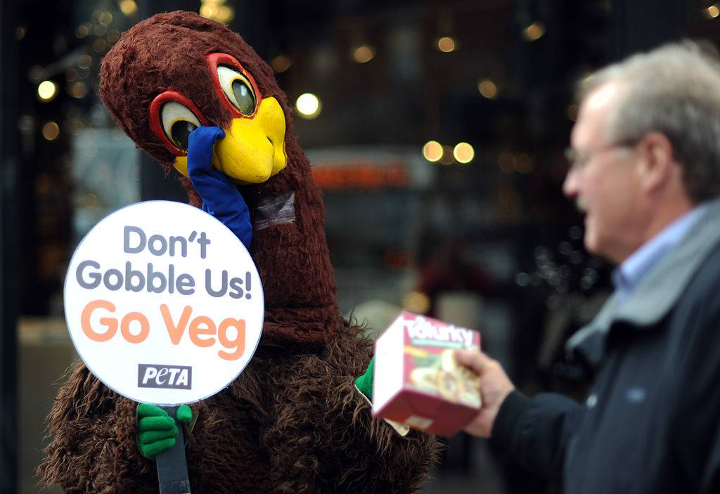 turkey mascot handing a box of tofurky to a man with a sign that says