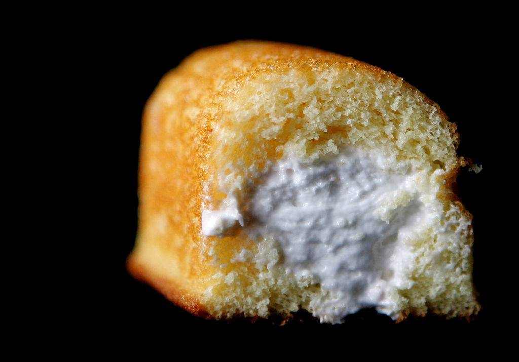 Part of a Hostess Twinkie golden sponge cake with its creamy filling exposed