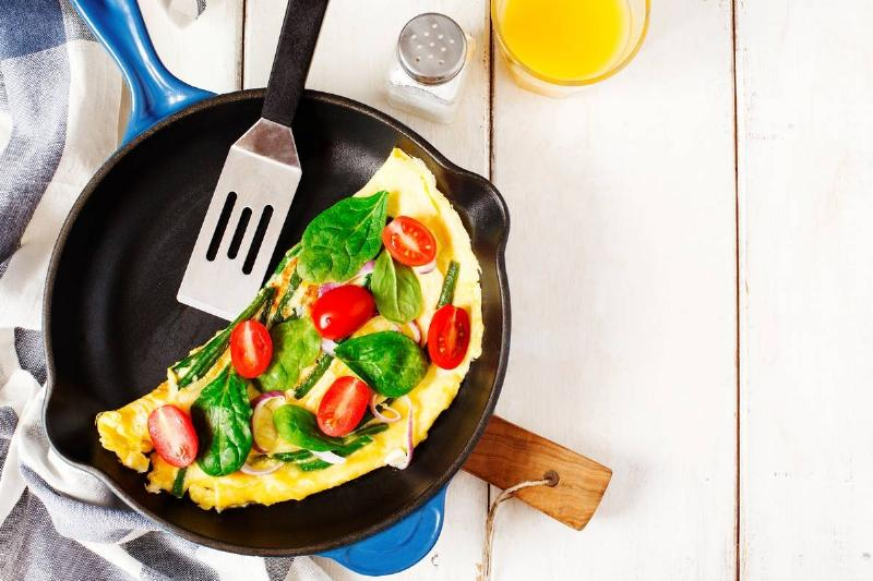Omelette with green bean. spinach and tomato in a skillet. top view