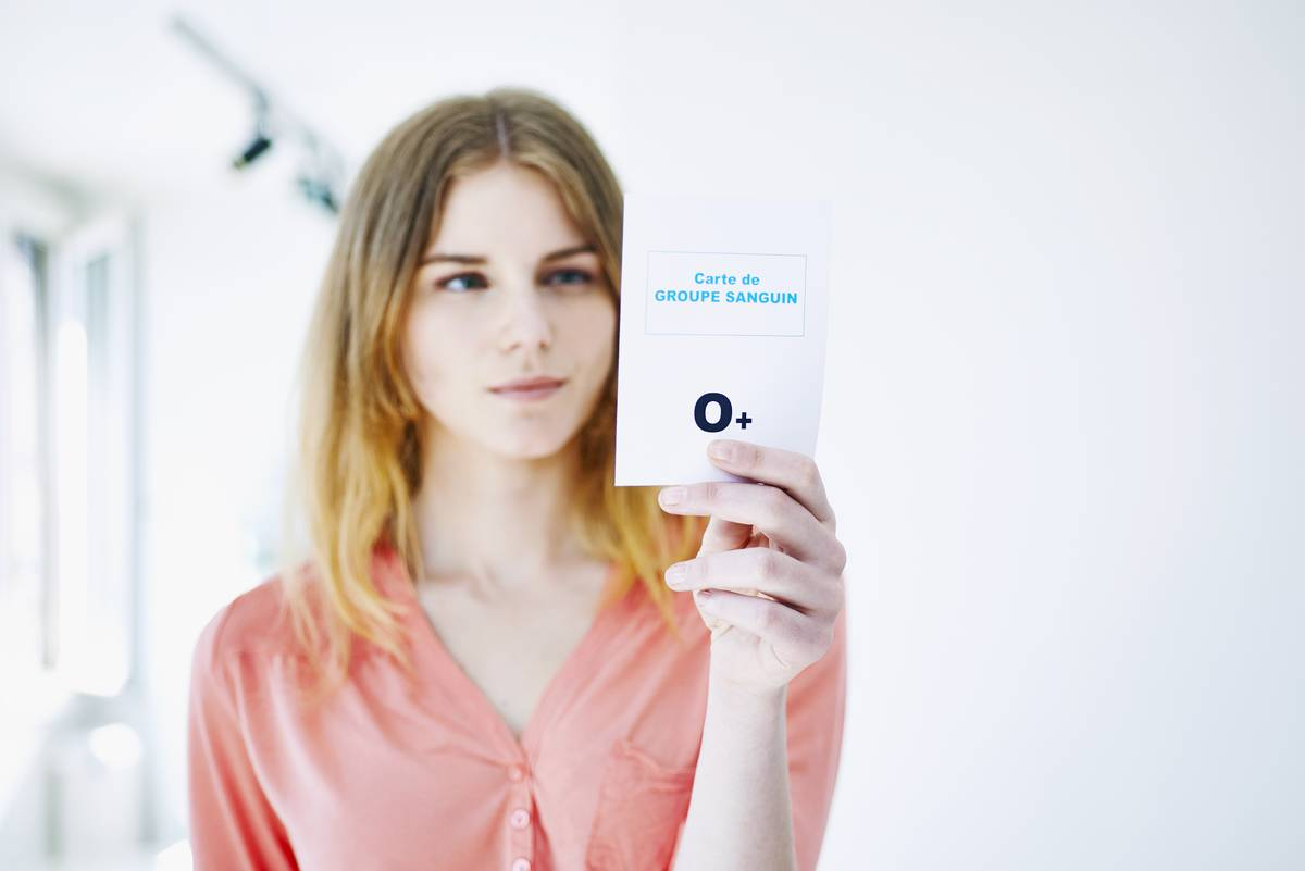 A woman holds up a card showing her blood type, O positive.