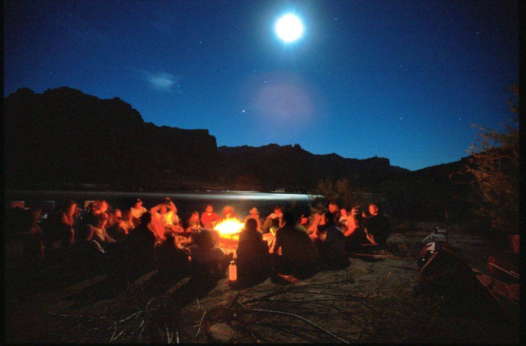 people sitting around a campfire in the moonlight