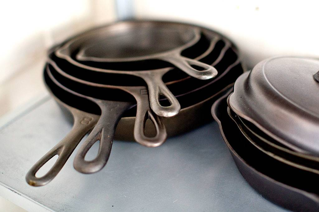 Cleaned and prepped cast iron skillets sit on a shelf