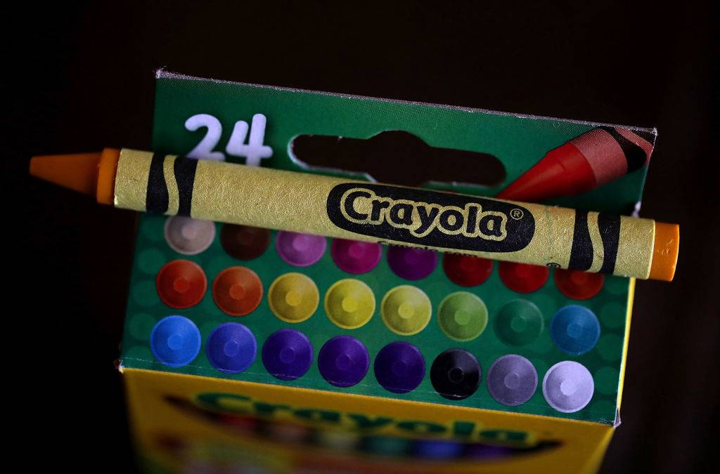 a yellow crayon on top of a box of crayons