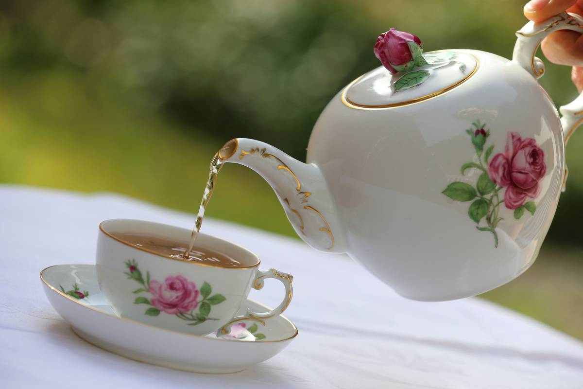 Black tea is poured from a kettle into a teacup.