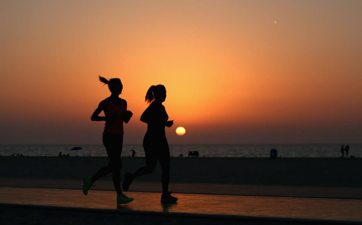 Two women jog together during sunset.
