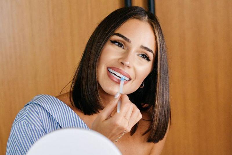 Olivia Culpo applying teeth whitener