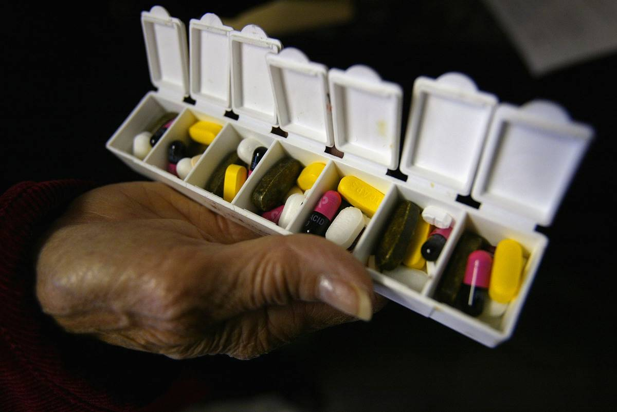 A woman displays her box of high blood pressure and asthma medications.