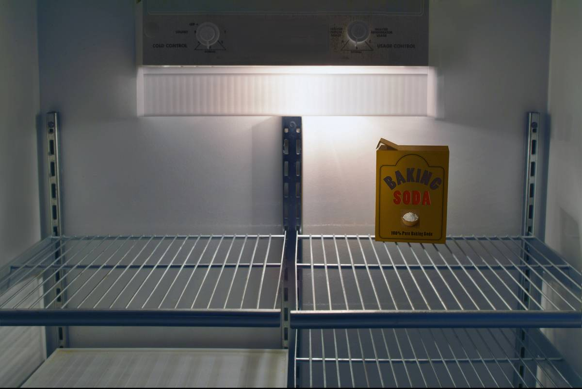 A box of baking soda is in an empty refrigerator.