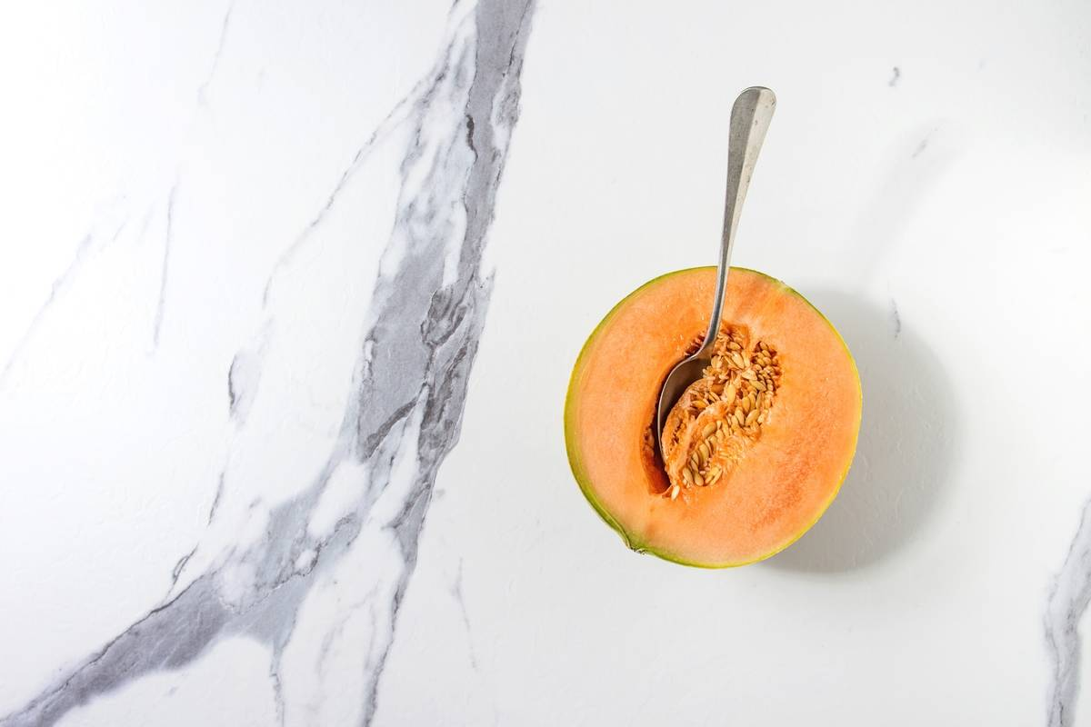 A spoon digs into a cantaloupe.