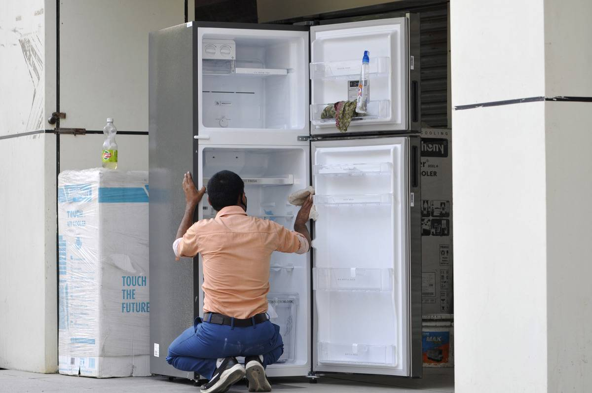 A man cleans an empty refrigerator.