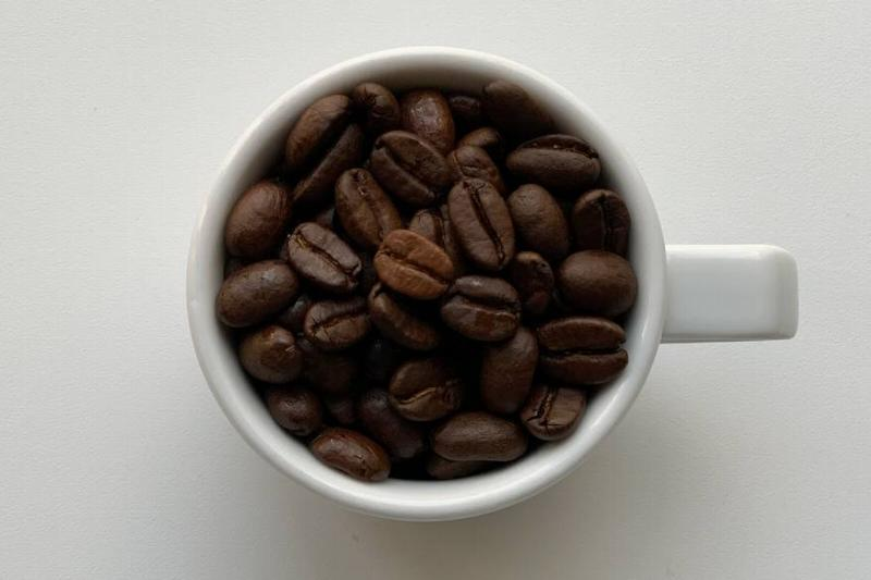 Whole coffee beans sit in a white mug.