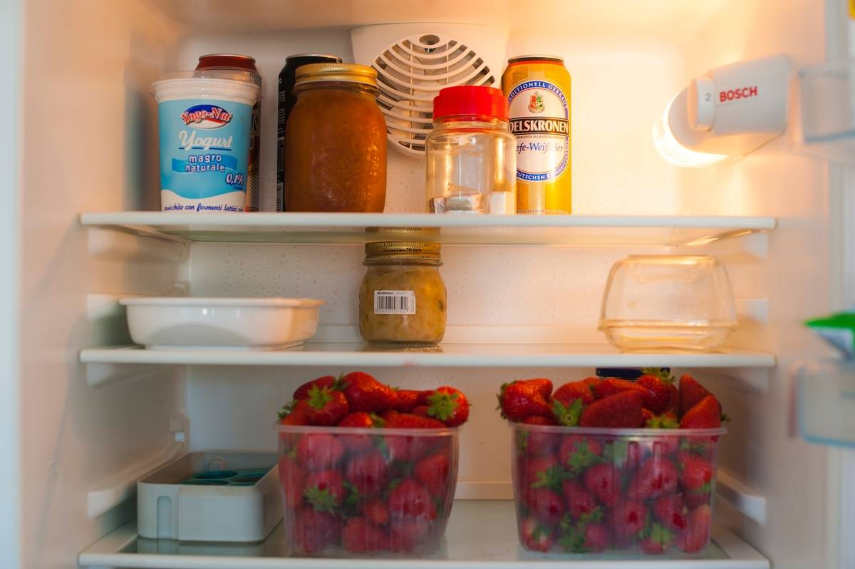 An organized refrigerator has food in containers.