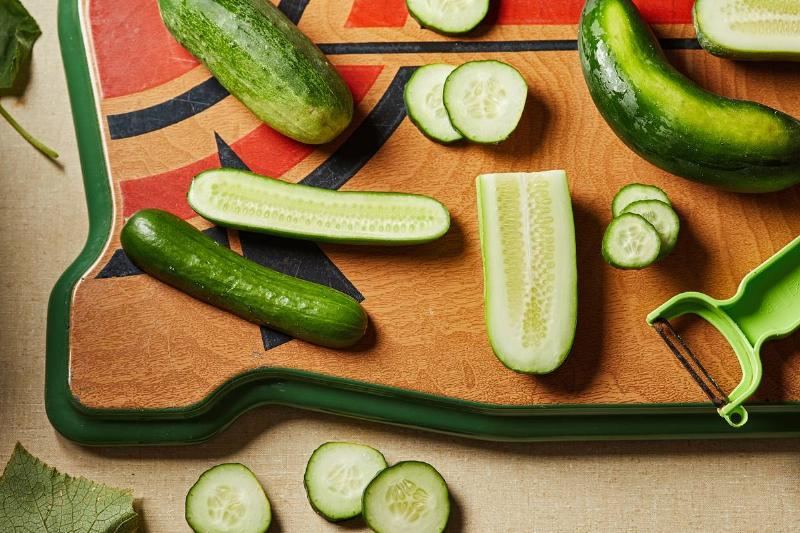 Sliced cucumbers lie on a cutting board.