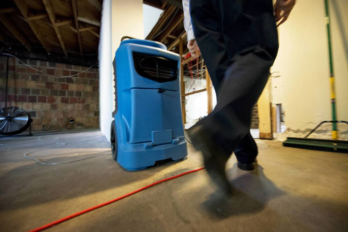 A person walks past a dehumidifier in his basement.