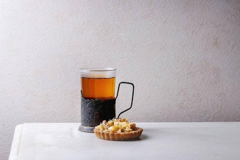 homemade-sweet-apple-shortbread-tartlet-in-white-plate.-glass-of-hot-tea-in-vintage-cup-holder-on-white-marble-table.-autumn-baking.-minimalist-style.-47651