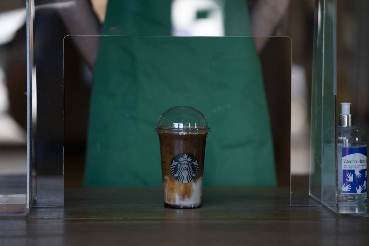 A Starbucks barista serves iced coffee.