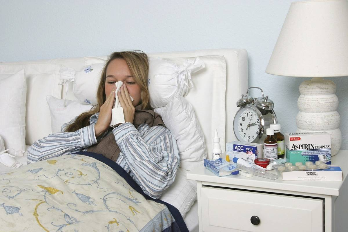 A sick woman blows her nose in bed.