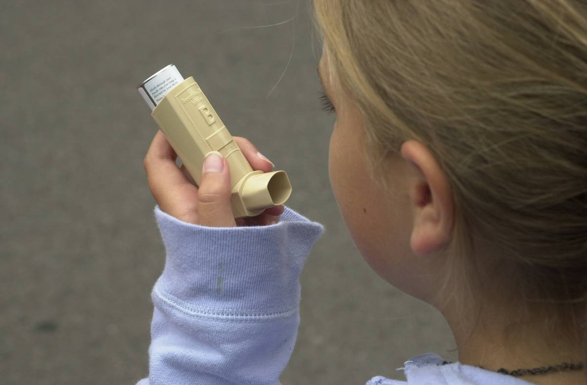 A young girl uses an asthma inhaler.