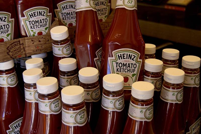 Several bottles of ketchup are stacked in a pile.