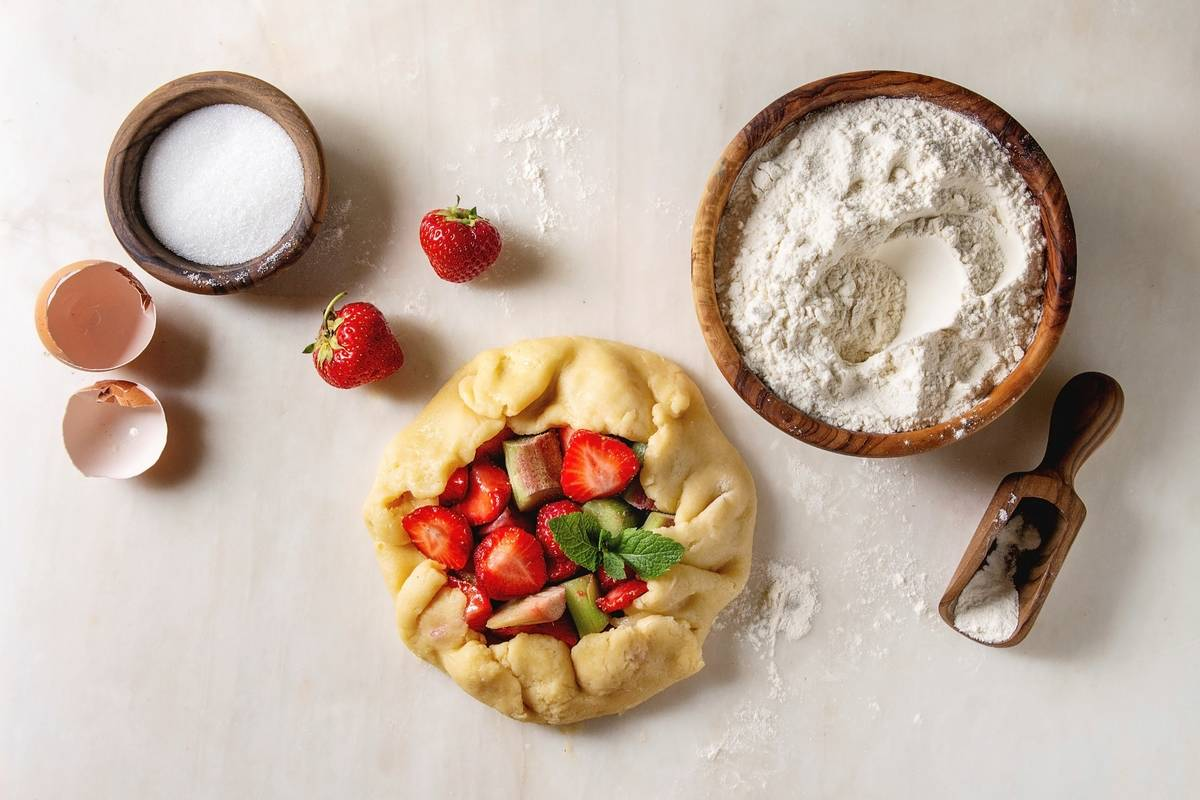 Process of baking summer berry biscuit pie. Bowl of flour. rolled shortbread dough. cutting strawberry and rhubarb. sugar over white marble background. Flat lay. space