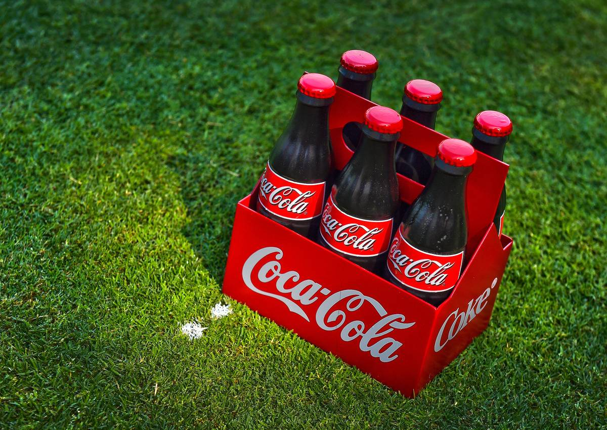 A six pack of Coca-Cola sits on the grass.