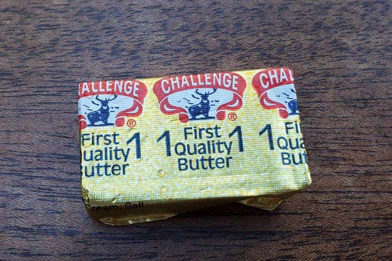 A small container of butter sits on a wooden table.
