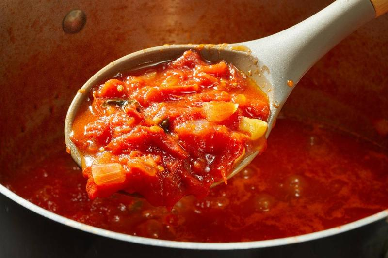 A spoon scoops tomato sauce out of a pot.